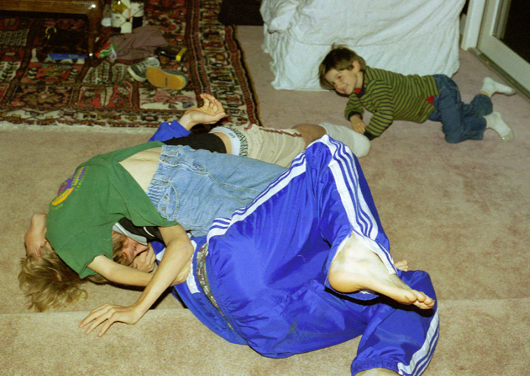 In this photo, Alex was refereeing a 2002 wrestling match between Alban and Charlie, on the one hand, and Nick on the other. After this photo was taken, Charlie says that Nick did a backflip and squished him and Alban. Note the shoes and clothes discarded behind the wrestlers, and the games also littering the living room floor.