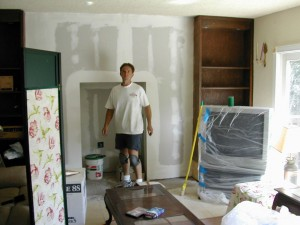 Here's Paul again a couple of years later, sheetrocking the new TV alcove while the TV waits, covered in plastic.