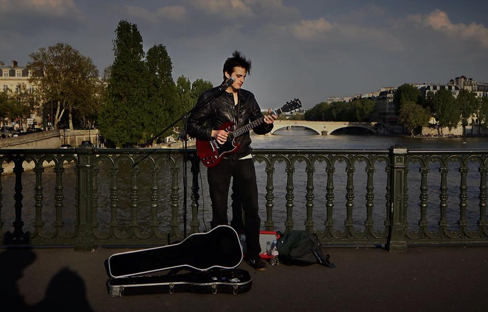 Tom busking on a bridge over the Seine. You too can suffer the privations of being a struggling young musician in Paris.